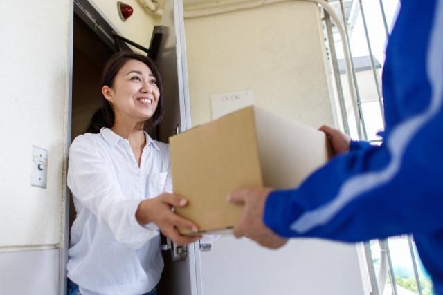 玄関で段ボール箱を渡す女性